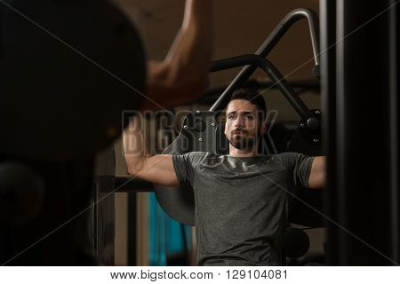 Young Bodybuilder Exercising Shoulders On Machine