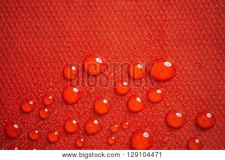 Water drops on red textile, close up