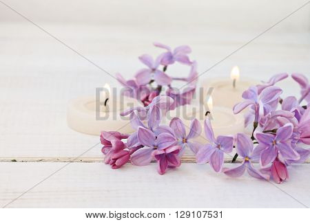 Candles and fresh lilac flowers. Soft light, soft focus.