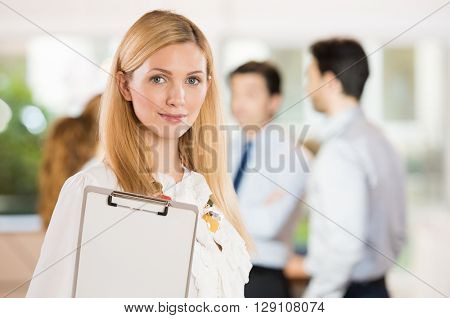 Portrait of beautiful businesswoman with others businesspeople in background. Confident business woman doing a questionnaire for a job interview recruitment.