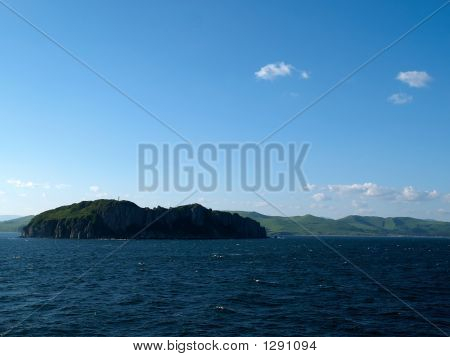 Rocky Island In The Ocean With Sky And Clouds