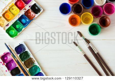 Art of Painting. Painting set: brushes paints crayons watercolor acrylic paint on a white wooden background