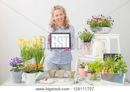 Woman gardener holding blank screen tablet and smiling