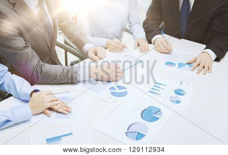 business and office concept - close up of business team with chats and graphs in office