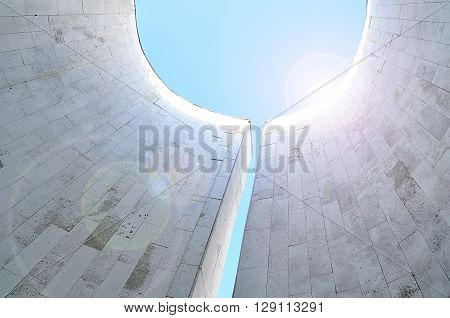 Perspective bottom view of semicircular walls of minimalist urban design -architecture futuristic background with reflected sunlights. Modern architecture cityscape with sunshine at the edge.