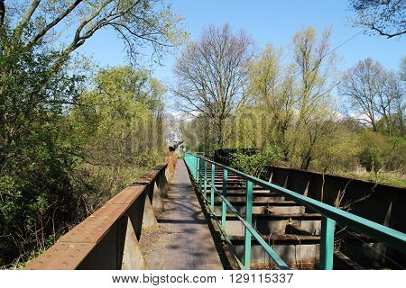 old abandoned railway bridge near Studenka, Czech Republic and some trees around it in spring