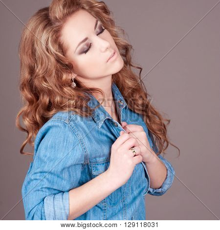 Beautiful young girl 20-24 year old wearing denim shirt over grey. Posing in room.