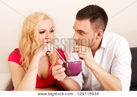 Cute couple drinking from one cup