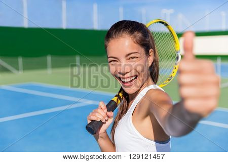 Happy Asian tennis player girl showing thumbs up hand sign after game fun holding racket on outdoor blue hard court for summer class. Sports ethnic young woman smiling of satisfaction.