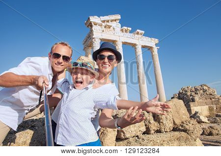 Positive young family take a selfie photo near antique ?olonnade. Temple of ApolloSideTurkey