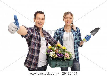 Studio shot of a joyful male and female gardener holding gardening equipment isolated on white background