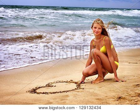 Summer girl sea.  Girl in swimsuit write on sand  heart shape . Summer vacation on sea.