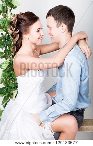 closeup of a young couple in love, man stands with his back to the camera, she bites his ear. Playful couple. her legs hugging man.