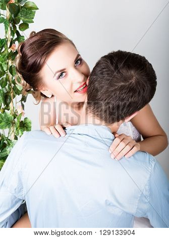 closeup of a young couple in love, man stands with his back to the camera, she bites his ear. Playful couple