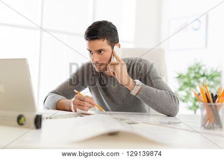 Young arabian male contractor sitting at desk in office using phone and analyzing blueprint. He looking at the laptop in front him.