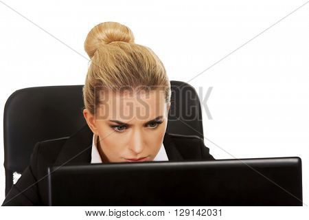 Surprised and curious businesswoman cannot believe what she sees in the laptop screen