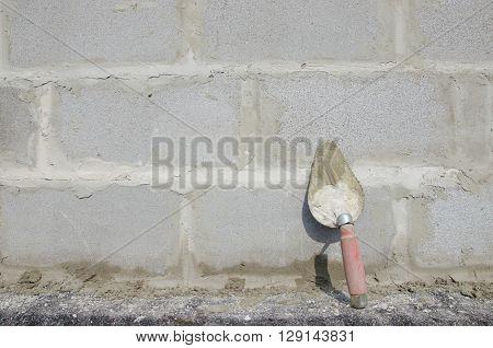 Trowel on cinderblock gray background. against the background of the brickwork is trowel