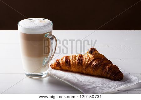 Glass of latte macchiato and French croissant on baking paper. Horizontal scene on white wooden background.