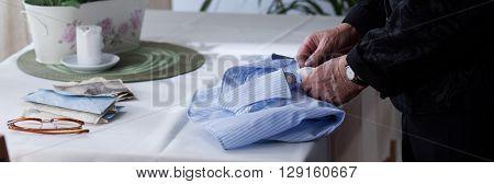 Elderly Woman Folding Men's Shirt