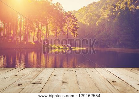 Wood Table And Pond Water And Sunrise With Vintage Effect.