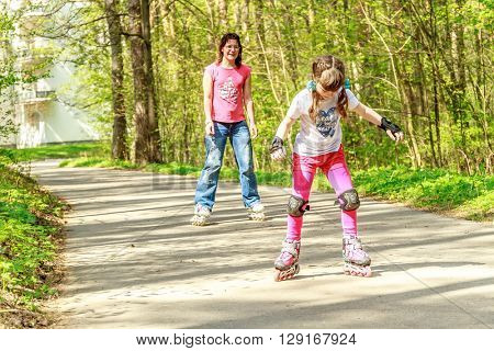 young girl in protective equipment and rollers scatung with mother in park, outdoor portrait