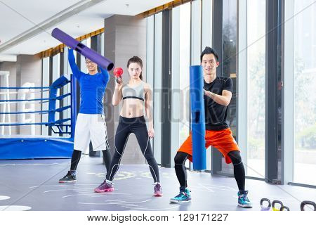 young asian people doing yoga in modern gym