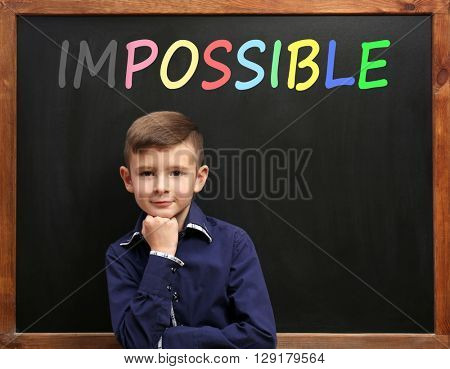 Schoolboy near blackboard with word impossible transformed into possible