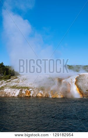 Streams of hot water and steam covering the Firehole river bank Yellowstone National Park