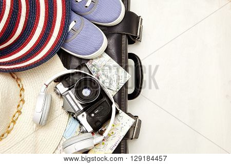 Vacation and travel items. Travel concept - headphones camera shoes map hat bag on a wooden background