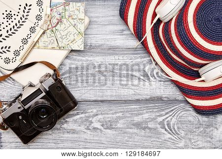 Vacation and travel items. Travel concept - headphones camera map hat bag on a wooden background