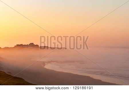 The town of Buffels Bay rising above the mist over sea in the first rays of the rising sun as seen from Buffelskop