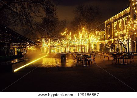 empty night restaurant, lot of tables and chairs with noone, magic fairy lights on trees like christmas, luxury lifestyle concept