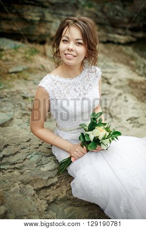 Beautiful bride with disheveled hair sitting on stones among rocks, wedding bouquet in hands. Candid portrait.
