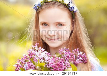 Cute kid girl 12-14 year old holding lilac flowers over nature background. Looking at camera. Childhood.