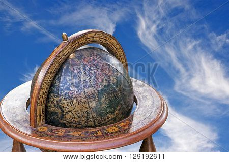 Mounted Retro World Globe Against Blue Cloudy Sky