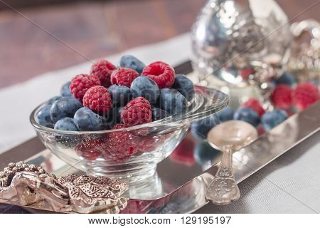 cream with raspberries and blueberries in a bowl on wooden background