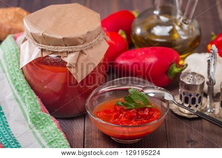 Appetizer of marinated red pepper and tomato sauce - lecho on rustic background