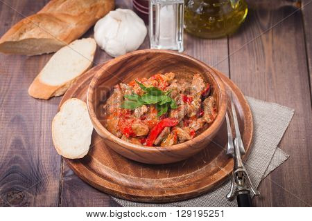 Meat stew with vegetables and herbs on old wooden table