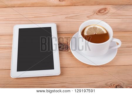 Tea with lemon and tablet computer on a wooden table.