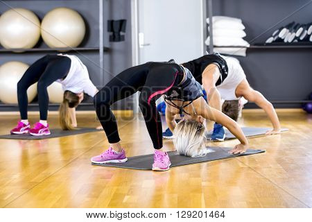 Workout team stands in bridge position in a pilates or yoga class. Flexibility and balance exercise at the fitness gym.