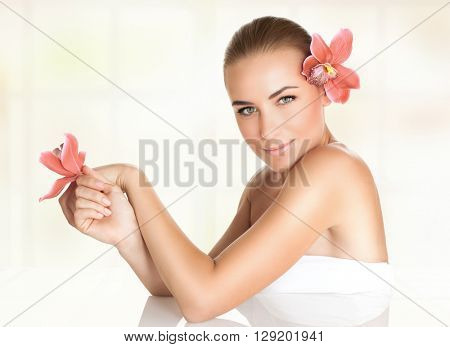 Pretty girl with orchid flowers in the hair and hand enjoying dayspa, body care, healthy lifestyle, beauty treatment in a spa salon, relaxation on massage table