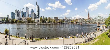 People Walk Along The River Main With Frankfurt Skyline