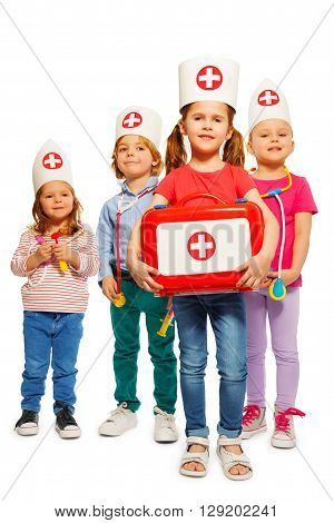 Four little doctors with medical box giving first aid, isolated on white