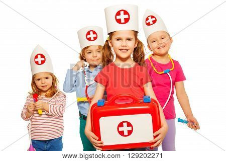 Four little kids with medical box and toy doctor instruments, isolated on white background