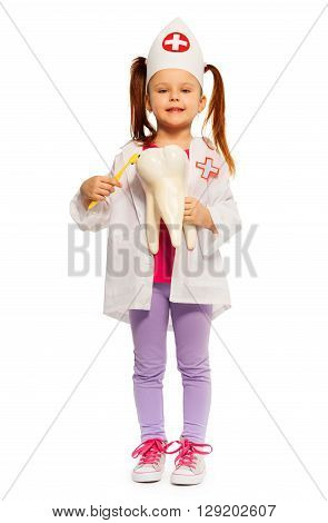 Cute little girl dressed as a dentist brushing big tooth dummy, isolated on white background