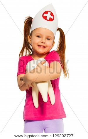 Funny little girl wearing a doctor cap with big tooth model, isolated on white background