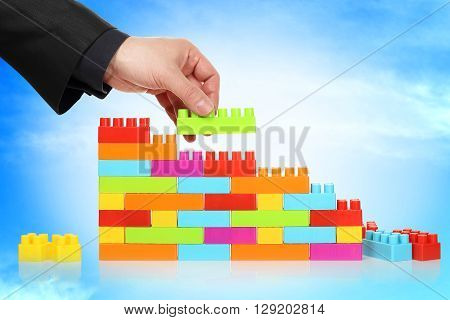 businessman adding toy block to a wall abstract concept