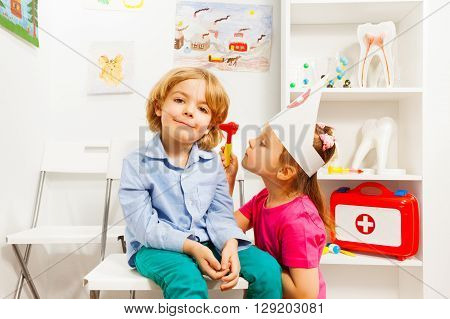 Cute girl playing ear nose throat specialist examining young boy with auriscope at doctor's office