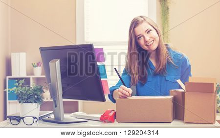 Young Woman Packing Boxes To Be Shipped