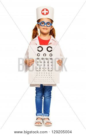 Young girl pretending to be a doctor dressed in doctor's costume and cap, wearing blue toy glasses, holding ophthalmologist's card isolated on white.